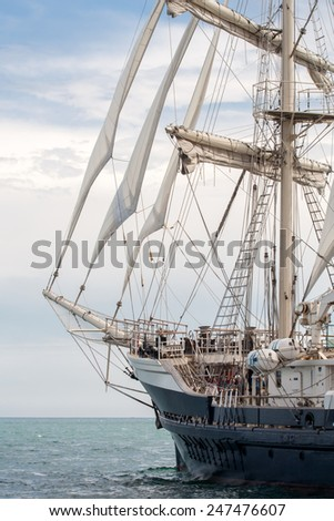 Old ship with white sales sailing in the sea