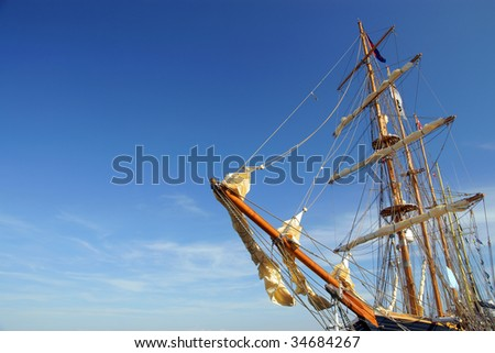 Old ship yard arm square rigging. Sailing ship's furled canvas sails and complicated rope