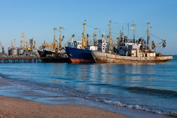 Old ships at the pier on the sea with an empty beach with clear blue water and sky. Seaport on the shore with cranes and boats. Wallpaper for desktop, poster, marine travel photo for post card design.