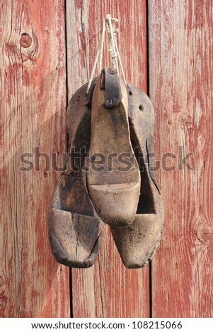 Old shoe lasts hanging on red wooden wall