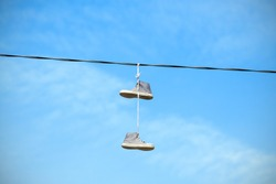 Old shoes hanging on an electric cable against blue sky.