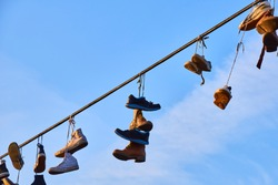 Old Shoes hanging on electrical wire against a sky