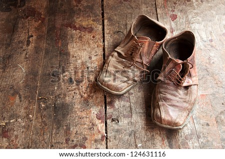 Old shoes on wooden floor. Pair of old dirty brown leather shoes.