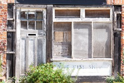 Old shop, unused and abandoned. Wooden front door and smashed boarded up windows. Unused and unowned.