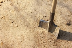Old shovel with wooden handle stuck in the sand / working tool in the environment