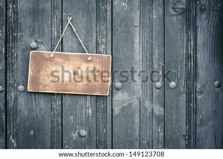 Old sign board blank hanging on vintage black wood planks background