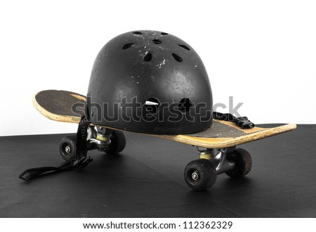 Old skateboard and worn helmet on black and white background