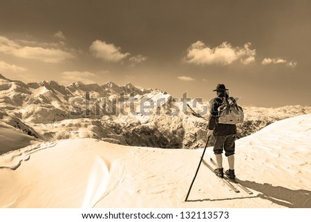 Old skier with traditional old wooden skis and backpack