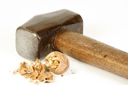 old sledge hammer and crushed walnut on a white background, excess force concept
