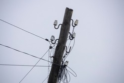 old sloping wood electric pillar against the grey sky. High quality photo