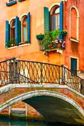 Old small bridge and old houses by canal in Venice, Italy