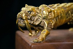 Old small gold tiger Statue in bronze. a fantastic figure made from bronze on black background. Antique bronze culture concept. brozen small statue or bronze sculpture.  tiger side, animal statues