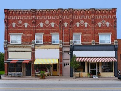 Old small town Victorian building with fancy brickwork and shops with awnings