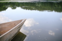 Old small wooden rowboat vessel boat stands by the lake or pond