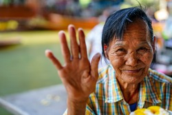 Old smiling Asian woman saying hello. Cute looking and courageous elderly woman wave hand, Thailand.