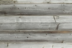 Old smooth unpainted boards. The wall of the house is made of boards. Horizontal view. Close-up. Background. Texture.