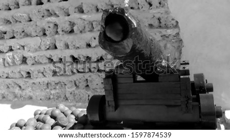 Photo of  Old smoothbore artillery cannon with a damaged barrel on a wooden pedestal on the background of the ancient fortress wall black and white
