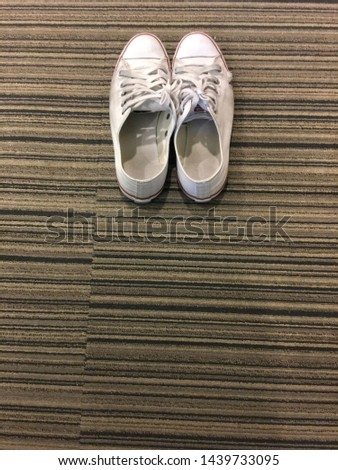 Old sneaker, white and dirty sneakers, isolate on the floor. Top view image. Vertical and copy space image.