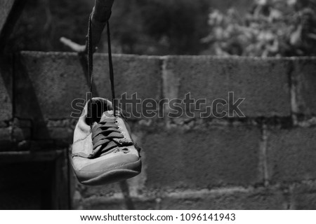 Old sneakers hanging on a rope, black and white picture