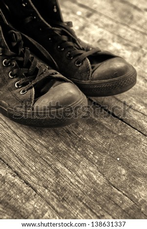 Old sneakers. Old black sneakers on wooden floor, monochromatic image. - stock photo