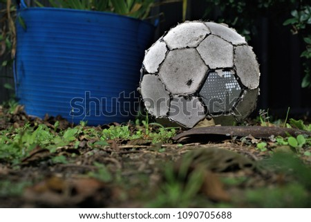 Old soccer ball lay on grass. Close up of worn out football. Fly can be seen sitting on soccer ball. Concept of inactive person or useless object
