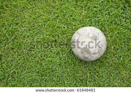 Old soccer ball on the green grass.
