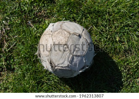 Old soccer ball. Top view. Classic soccer ball on the grass. Broken and used soccer ball Stockfoto ©