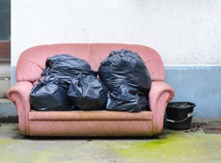 Old sofa with black sack on top.