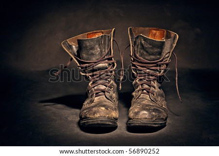 old soldier's boots worn with scratches and untied shoelaces on dark background