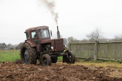 Old Soviet AWD wheeled brown diesel tractor with exhaust smoke plowing the field on backyard close up, soil cultivation on an autumn day on woden fence background, rural agriculture farming landscape