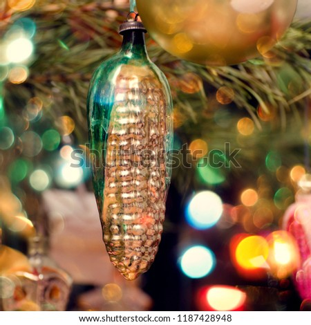 Old Soviet Russian christmas and new year decor on a fir tree branch. Yellow corn made of glass.