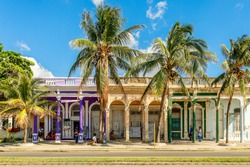 Old Spanish colonial colorful houses with palms in the foreground, across the street in the center of Cienfuegos, Cuba