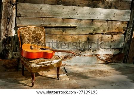 old spanish guitar on an old armchair horizontal