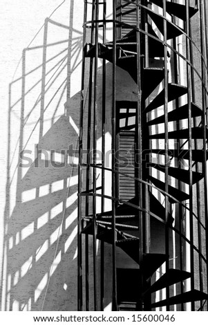 old spiral fire escape stairs, black and white photo - stock photo