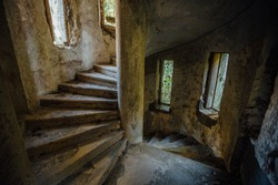 Old spiral staircase in tower of abandoned mansion.