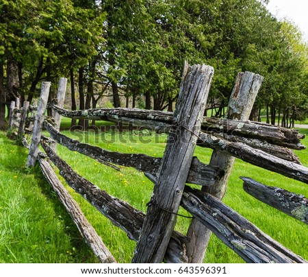 old split rail fence  gray with age and covered with lichen creating boundaries   #643596391