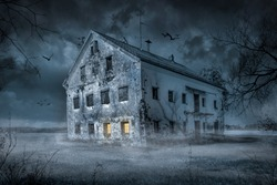 Old spooky abandoned farm house in moonlight