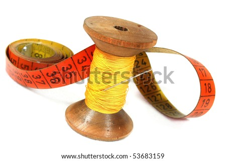 old spool of thread with needle and measuring tape on white background