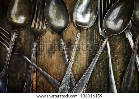 old spoons and forks on a wooden table - stock photo