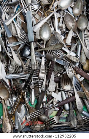 old spoons, teaspoons, knifes and forks in a box on a flea market