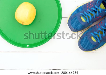 Old sport shoes and dumbbell on a white wooden background. Sport equipment top view