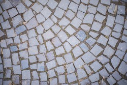 Old square stone tiles on the road and sidewalk, old style stone paving stone masonry, stone dirt road in the old town, laying slabs on the roads