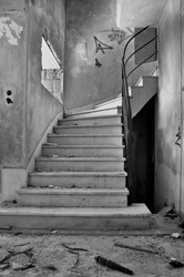 Old staircase and dirty floor in abandoned building interior. Black and white.