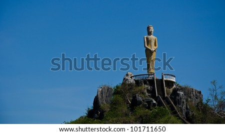 old status image of buddha standing on mountain in Thailand