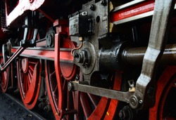 Old steam engine perspective of a railway locomotive with metal details of the machinery, screws, pipes, wheels, cylinders, linkage struts, connecting rods in red and black color with oiled parts