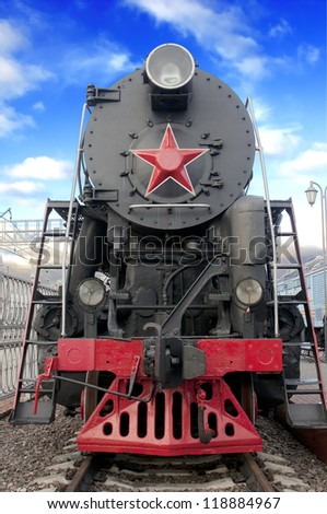 Old steam locomotive against blue sky - stock photo
