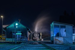 Old steam locomotive being fired up in front of a turntable during the night. Romantic photo of a steam engine during the night.