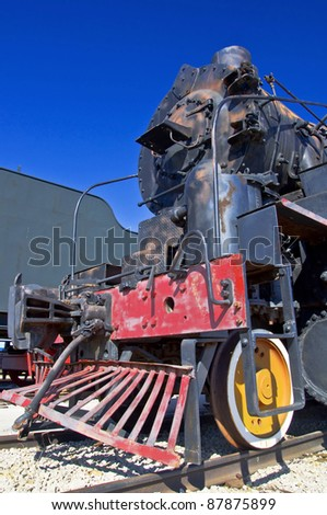 Old steam locomotive in the background of blue sky. Close-up. - stock photo