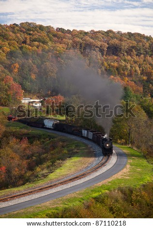 Old steam locomotive pulls freight through rural countryside in autumn