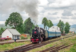 Old steam locomotive with blue cars at the train station in the mountains. Ancient black locomotive with a red star departs from railway station in mountain pass in Carpathians, Ukraine